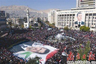28日,上万名叙利亚民众在大马士革举行抗议阿盟经济制裁的示威游行。新华社发
