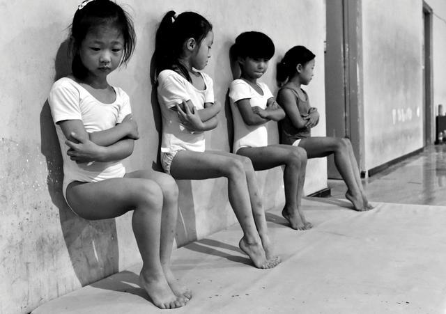 荷赛日常生活类单幅二等奖《汗水铸就中国梦》(Sweat Makes Champions)。中国徐州,一所体操学校的四名学生在做下午30分钟的脚趾压力训练。王铁君
