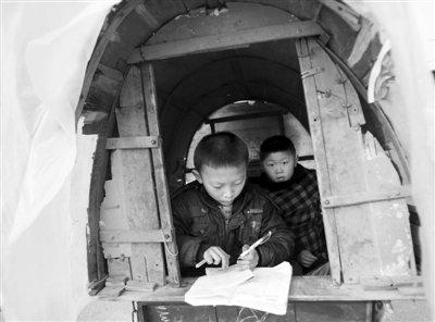 昨日,江苏丰县首羡镇,几名放学的孩子在三轮车内做功课。当地校车停运后,家长用三轮车接送孩子上学。郭铁流 摄