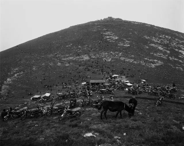 2007年4月19日,河南省宜阳县。一位村民在停满摩托车的山坡上放马。