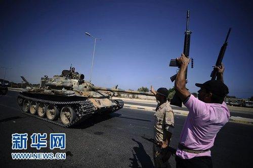 8月21日,一名利比亚反对派武装人员在利比亚首都的黎波里西部地区举起手中的武器。新华社/法新