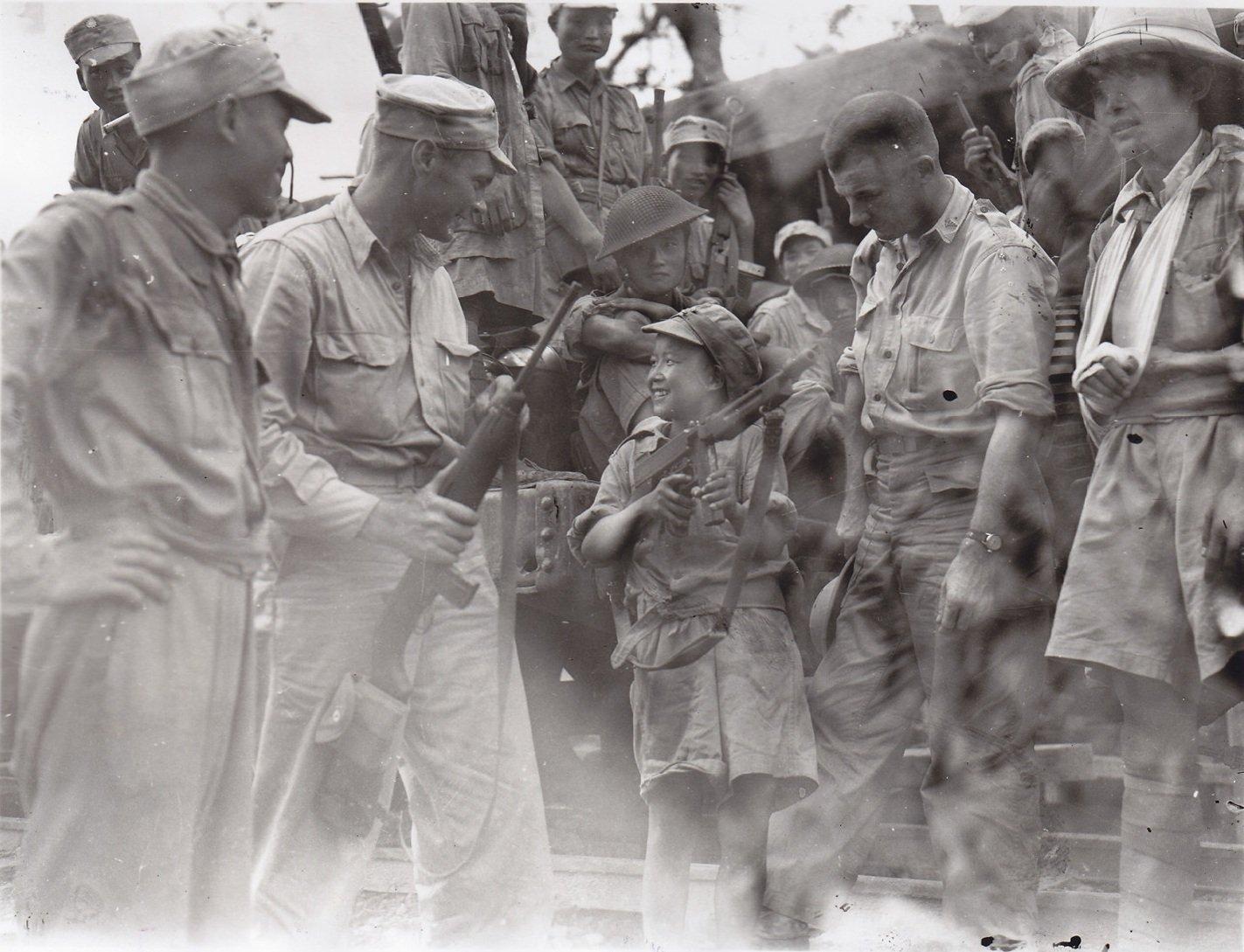 中国军队第14师42团里最年轻的士兵――上等兵李乐贝(音),云南人,年仅12岁,已经入伍一年。美军联络官声称李曾经站着连续向日军投掷了两整箱手榴弹,消灭了很多日军。此刻,他正与两名美军联络官讨论他的冲锋枪。从左到右为,来自俄克拉荷马州阿德莫尔的步兵联络官莱缪尔・约翰逊上尉,华盛顿州塔库玛的医疗联络官克里斯滕森上尉。阿莫尔五级技术军士拍摄于1944年9月12日。