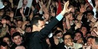 叙利亚总统巴沙尔(中)在议会发表演说后向聚集在议会大厦对面街道的群众致意。