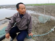 渔民看着干涸的湖面一筹莫展