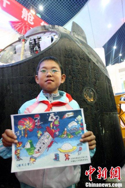 11月21日,神舟八号返回舱开舱仪式在北京航天城举行,一名北京小学生在返回舱前展示自己的画作《航天之梦》。中新社发 张浩 摄
