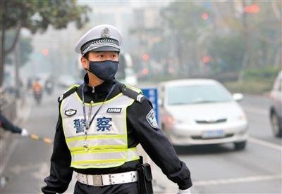 昨日,一名交警佩戴口罩在宁波街头执勤。新华社发