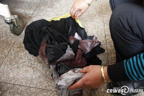 周林母亲向记者展示周林替换下来的衣服,上面沾满了血迹。(摄影 王莹)
