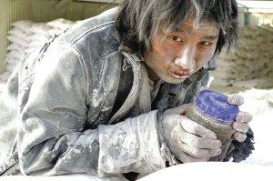 这位工人抱着一个水杯在成品大白粉堆上发呆。