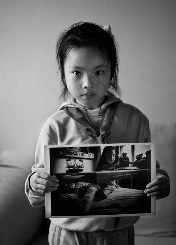 """2009年5月7日,四川省江油市。""""汶川地震""""1周年,地震幸存者8岁的梁可馨拿着地震后在医院病床上拼房子积木的照片。现在,她是胜利街小学学生。"""