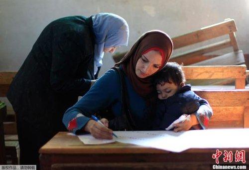 图为埃及开罗,一名妇女抱着孩子在投票点阅读选票。