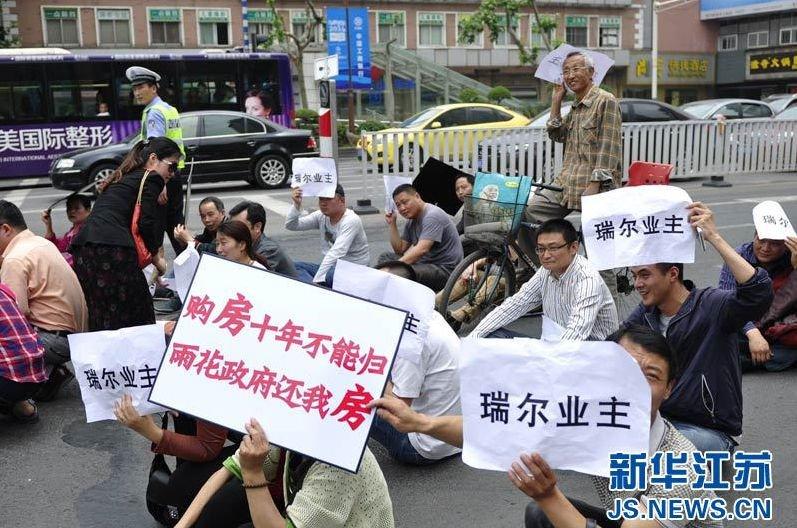 高清图—南京瑞尔大厦烂尾楼业主30人在中山南路静坐抗议