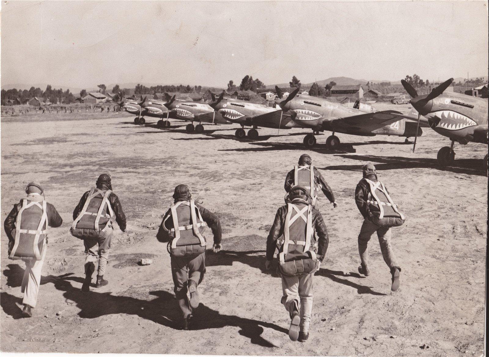 当空袭警报拉响时,穿戴好降落伞的美国飞行员们飞快跑向他们的战机,升空驱赶来犯的日军飞机。这些驾驶美国飞机的队员在飞机引擎下方做了鲨鱼鼻的涂装,以此奚落害怕鲨鱼的日军。拍摄于中国,1943年1月13日。