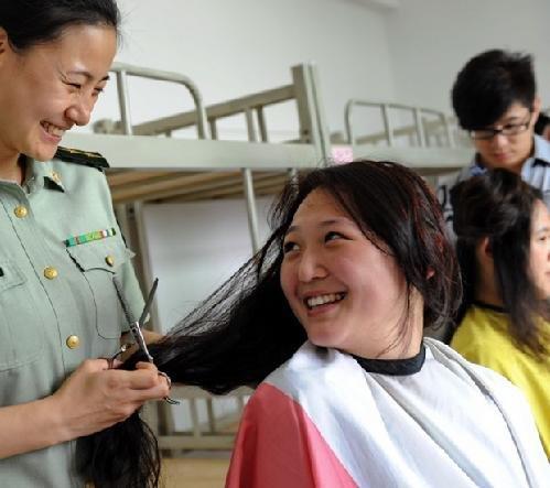 2011年7月14日,河北省公安边防总队教导大队女警官给入伍大学毕业生图片