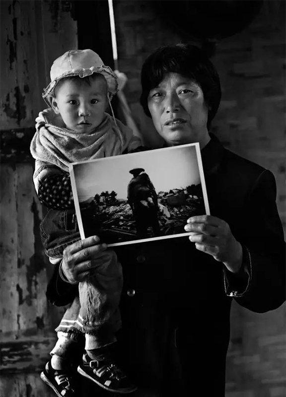 """2009年5月6日,四川省彭州市通济镇桥楼村。""""汶川地震""""1周年,地震幸存者60岁的曹良英和地震幸存者1岁半的孙子罗远航拿着地震后望着家园废墟的照片。"""
