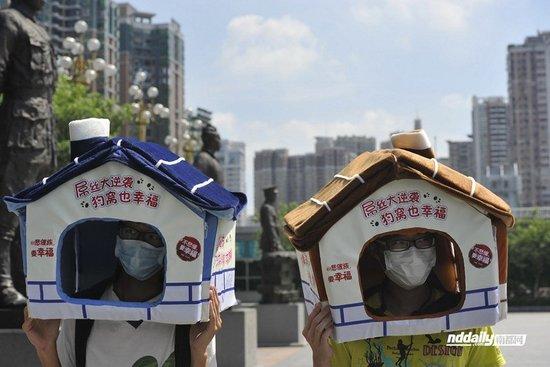 12日下午,3名来自广州的大三学生头顶着狗窝,在越秀区英雄广场上一字排开,抗议高房价。