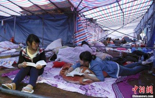 4月25日,四川宝兴中学体育场上,两位高二的女生在帐篷里看书。中新社发 张浩 摄