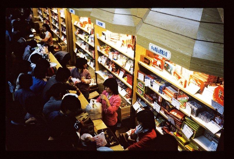 20世纪70年代末的广州,正处在改革开放的前沿,人们的视野变得开阔,想法越来越多元化。随着经济的复苏,市场变得日益活跃,票证制度、定量供给制度的取消使物质商品丰富,整个城市透出蓬勃的生机。图为拥在柜台前选购商品的顾客。