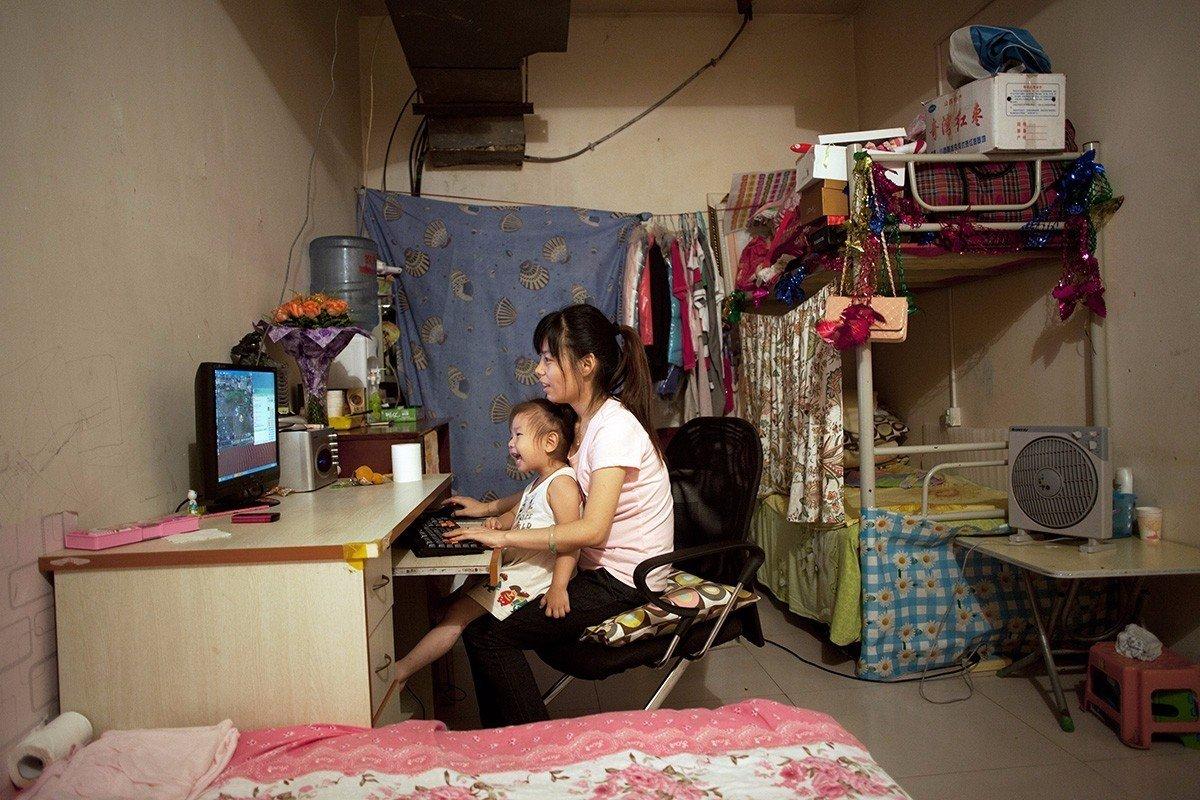 在北京西部的地下室中的最大的一间房子里,25岁的季兰兰(音译)与她3岁的女儿正在玩游戏。季兰兰已经在这里住了四年了。《北京地下的蜗居世界》,北京,2011