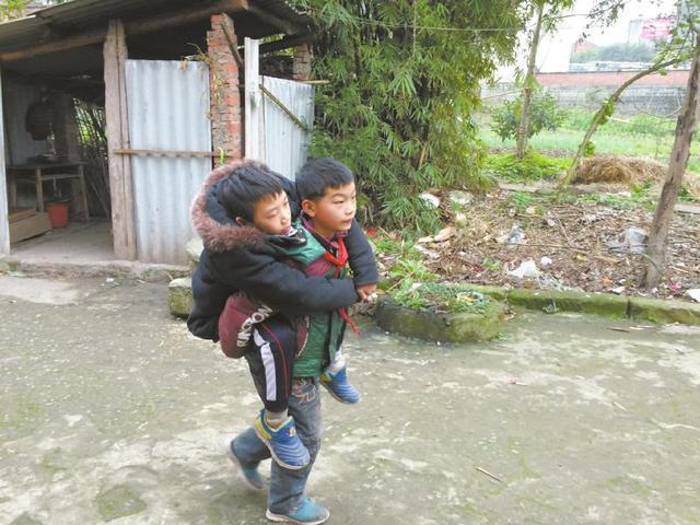 8岁叔叔背13岁残疾侄儿上学 风雨无阻(组图)