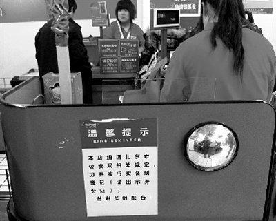 一家超市在收银台贴出提示,提醒顾客购买刀具须出示身份证。本报记者 周鑫 摄