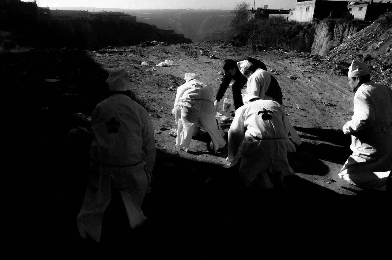 男系子孙端着食物和酒,点香烧纸,在原上山头祭拜。