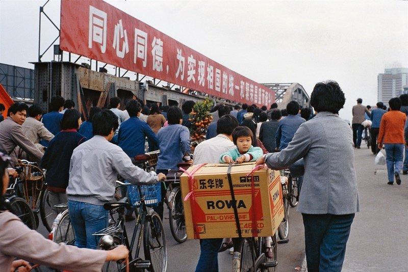 70年代末80年代初开始,电视机开始走进人们的家庭,带来了更多信息和外面世界的面貌。图为一位市民把刚刚购买的彩色电视机放到自行车后座上拉回家。