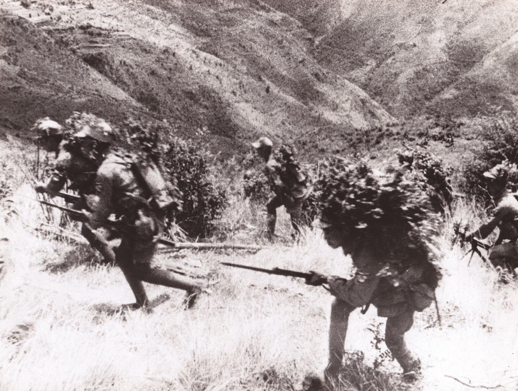 在一次阻击日军进攻的战斗中,中国士兵在掩护下向山上冲锋。拍摄于缅甸边境一侧的怒江沿岸,1943年6月22日。
