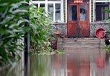 一位大娘望着屋外深深的积水