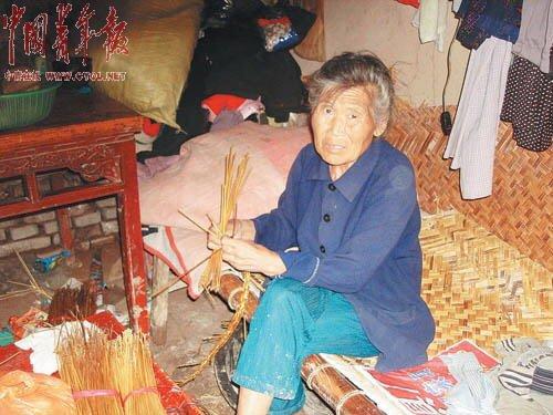 9月7日上午,张振风的母亲正在编织草帽辫。她的丈夫不愿对记者多说。本报记者 刘万永摄