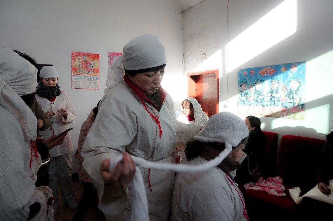 """参加葬礼的女人们按照传统在准备着孝服。孝服用的是极粗的生麻布,穿戴孝衣孝帽谓之""""成服"""",亦称""""戴孝""""。"""