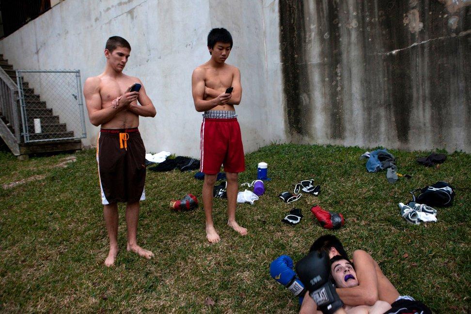 """当地时间2011年1月5日,美国德克萨斯州奥斯汀,高三学生Bryan Campbell和Jheh Chow用手机录制Clay Hughto摔跤时被对手肘部压制的视频。几名学生每周或每月聚集在Bryan家中参加""""搏击俱乐部"""",练习拳击和摔跤。"""