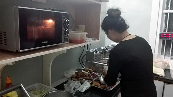 汉堡奶茶店老板娘武成会在后厨,准备夜宵时间要卖的汉堡和小食。