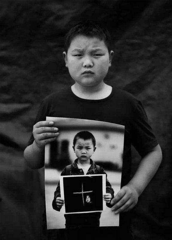 """2014年5月3日,四川省彭州市通济镇桥楼村。""""汶川地震""""6周年,地震幸存者12岁的刘世杰拿着地震1周年时拍摄的肖像。现在,他是镇小学5年级学生。"""