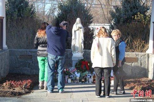 12月15日,美国康涅狄格纽敦的民众在本地天主教堂的圣母像前为发生在当地的校园枪击案死难者肃立默哀。中新社发 李洋 摄
