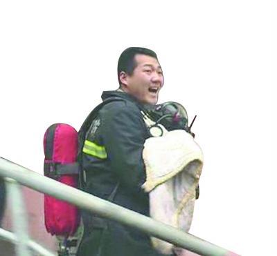 """消防员付一帆抱着""""面罩婴儿""""冲出火场喊人接应。"""