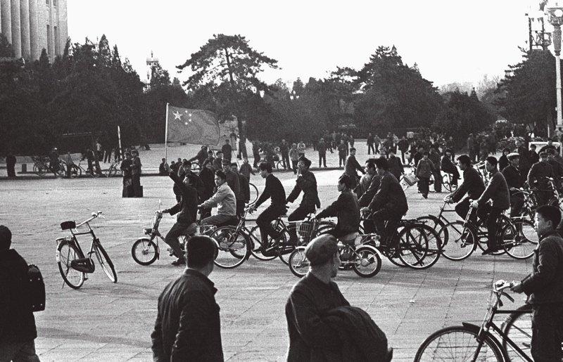 """20世纪80年代是中国女排的鼎盛时期,主教练袁伟民和郎平、孙晋芳、陈招娣等队员为中国女排赢得了第一个世界冠军,这同时也是中国三大球项目的第一个世界冠军。图为女排夺取""""四连冠""""的消息激动人心,北京市民来到广场挥舞着国旗,表达激动的心情。"""