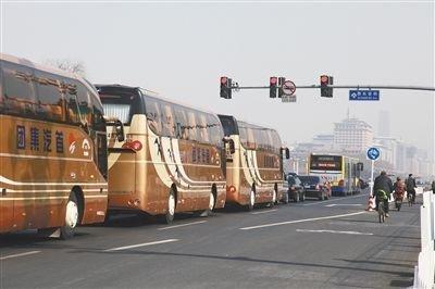 今年3月3日下午,北京,前往人民大会堂的大巴车队在西长安街上等待红灯。图/CFP