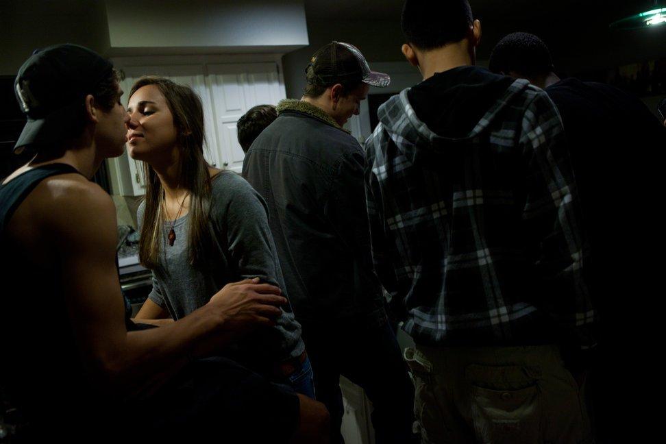 """当地时间2010年11月11日,美国得克萨斯州奥斯汀,安德森中学的高中生Chantal Curry与Zachary Flores在Zachary家举办的派对上亲吻。派对为庆祝安德森校足球队踢赢了奥斯汀高中足球队。派对上,学生们在玩""""啤酒乒乓""""。"""