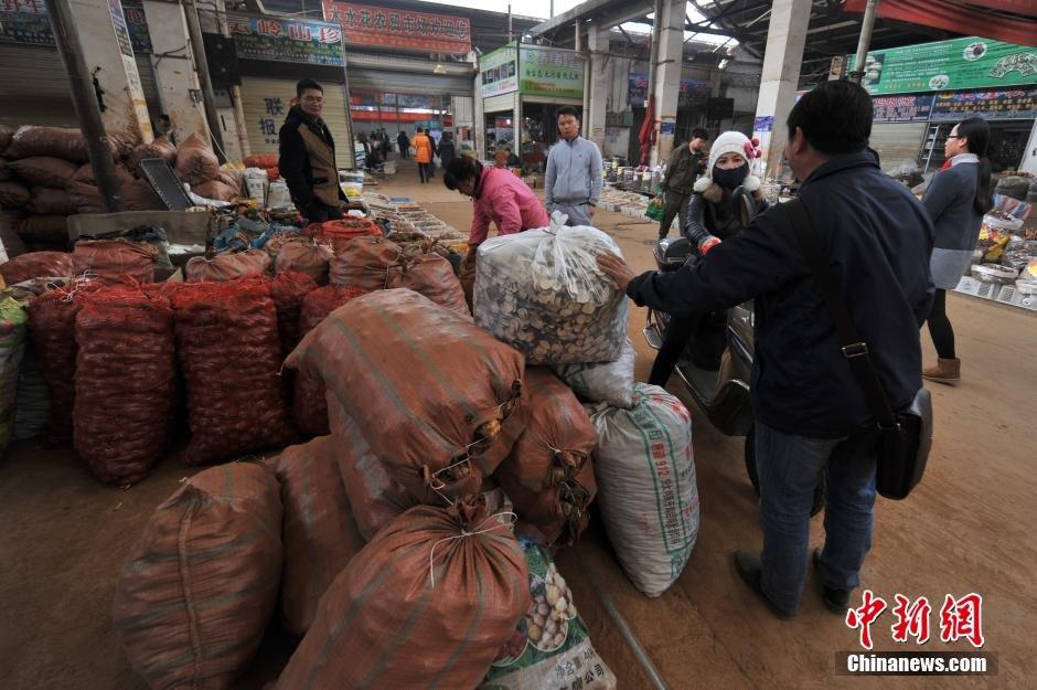 昆明木水花野生菌交易市场里,售卖玛卡的商人与顾客还价