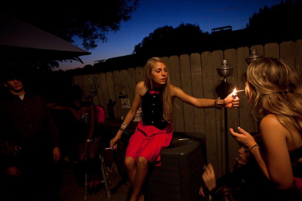 当地时间2010年10月16日,美国德克萨斯州奥斯汀,Callie Carson(中)为朋友点烟,她在朋友家中参加返校节舞会。