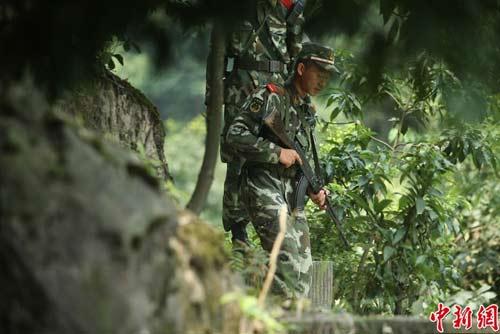 图为武警官兵提着枪支搜寻犯罪嫌疑人踪迹。
