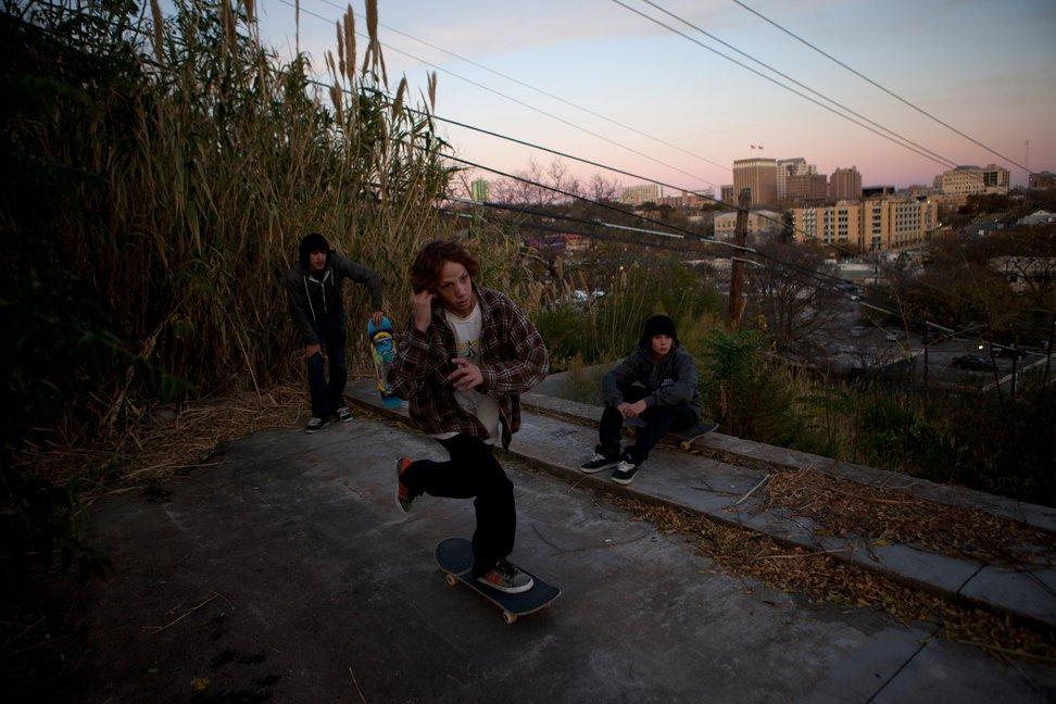 """当地时间2010年12月12日,美国得克萨斯州奥斯汀,滑板青年Alder Wilson(中)、James Cameron和Jason Dominguez在城堡山上玩滑板。这里是当地年轻人的""""秘密据点"""",可俯瞰奥斯汀。"""