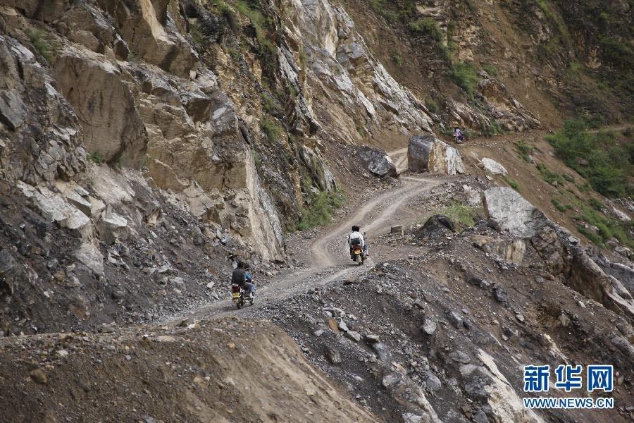 ,云南省昭通市鲁甸县龙头山镇银屏村的村民乘摩托车向安全区域转图片