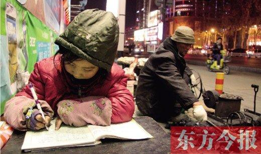 高清图—平顶山9岁女孩齐聪聪寒夜街头卖爆米花 露天写作业