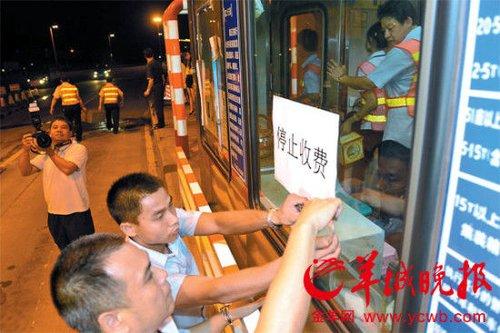 """沙湾大桥收费站工作人员在张贴""""停止收费""""告示 羊城晚报记者 林桂炎 摄"""