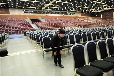 昨日,国家会议中心大会堂,一名服务员在以线为参照物摆齐凳子,屋顶的灯全换成LED灯。新京报记者 秦斌 摄