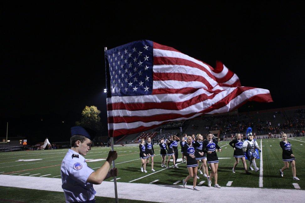 当地时间2010年11月12日,美国得克萨斯州奥斯汀,安德森高中的啦啦队为比赛做准备,Chuck Metula拿着美国国旗站在一旁。