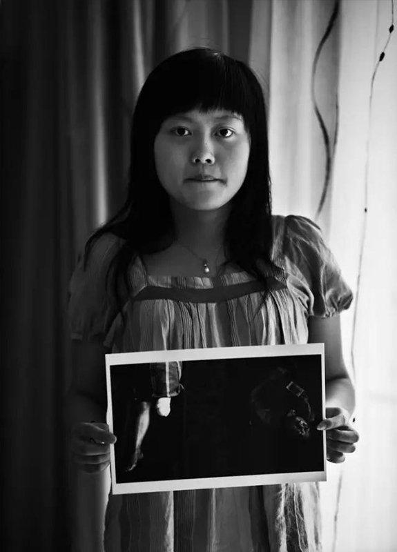 """2009年5月7日,四川省绵阳市。""""汶川地震""""1周年,地震幸存者19岁的龚悦拿着地震受伤后躺在火车站站台上的照片。当时,她是北川中学学生。"""