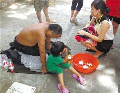 """3日,南京,小女孩正坐在路边乞讨,身旁跪着她的父亲。面对救助站社工的询问,男子不作任何解释,只是不断重复着""""这是我的孩子,我不需要救助""""。 王宇清 摄"""