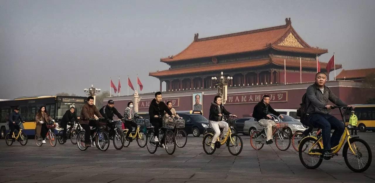 2017年3月29日,北京,中国的上班族们正使用共享单车骑过天安门广场。摄影:Kevin Frayer